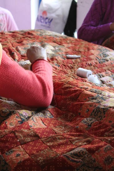Gudri Work - A Woman making Gudri Quilt